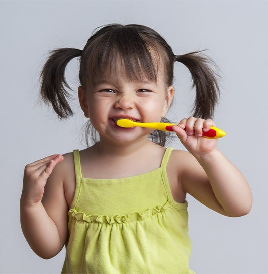 Young girl practicing tooth brushing