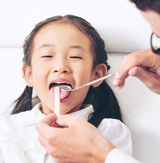 A dentist uses dental instruments to perform an oral cancer screening on a little girl