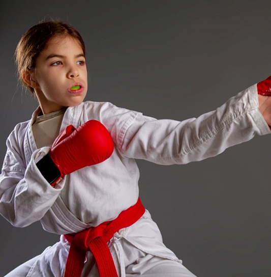 A young girl wearing a white robe, red belt, and red boxing gloves while protecting her mouth with a sportsguard