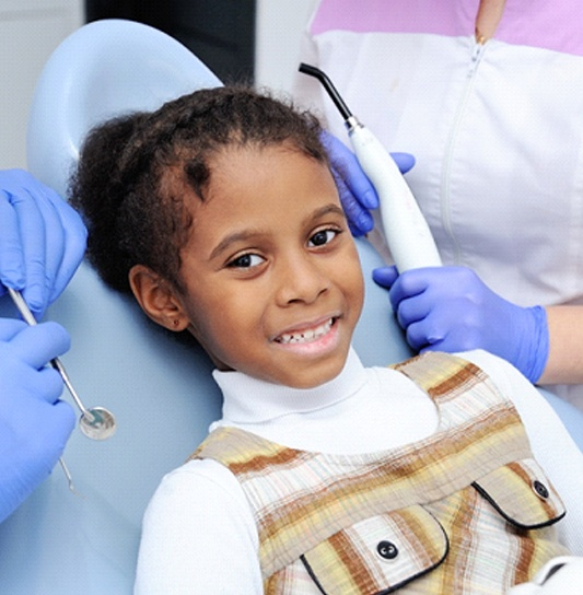 A little girl wearing a plaid jumper and white shirt smiles while a dentist and their assist prepare to check her smile