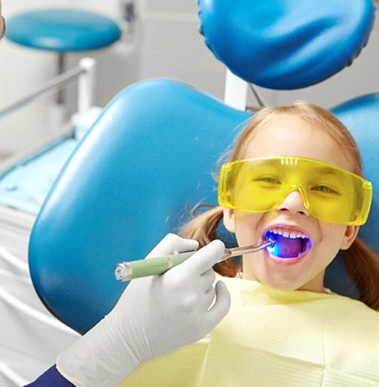 A dental hygienist uses a special light while applying a tooth-colored filling to a little girl's smile