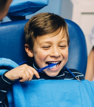 Young boy in dental chair practicing tooth brushing