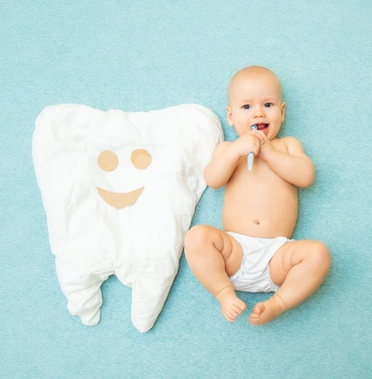 A baby wearing a pair of bloomers and brushing its teeth while lying next to a large tooth pillow