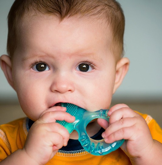 A baby boy holding a solid teether in his mouth to help with the teething process