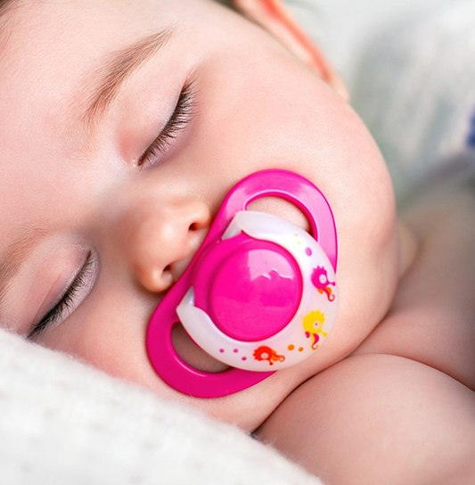A baby asleep in bed with a pink pacifier in its mouth