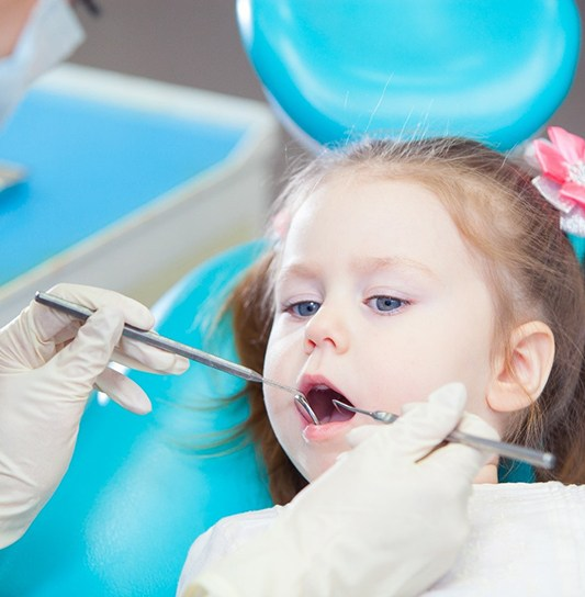 A dental hygienist examining a little girl's smile before administering fluoride treatment
