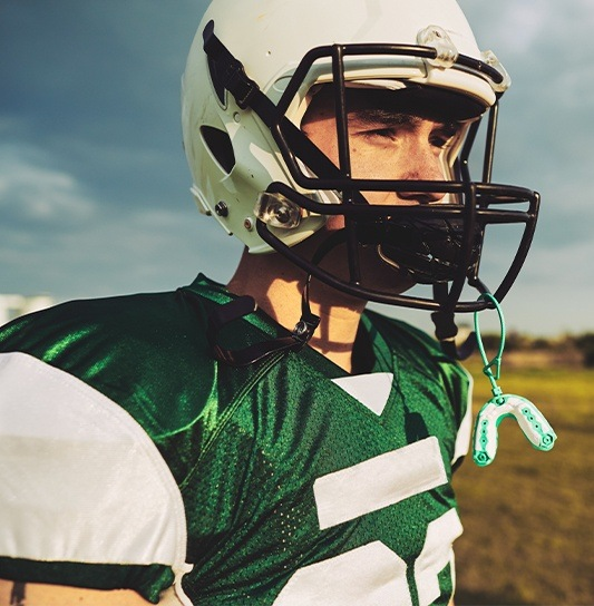Teen boy with athletic mouthguard on helmet