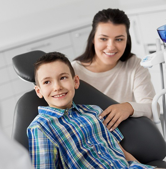 Young boy and his mother smiling together in dental office