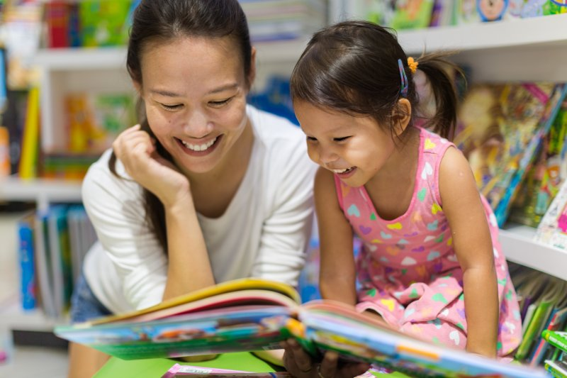 a mother and daughter having fun while reading books about dental visits